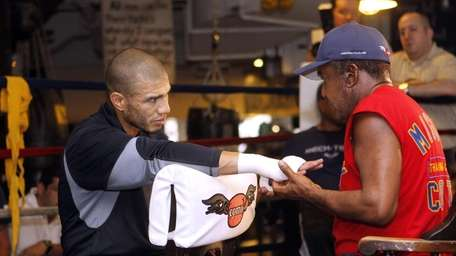 Boxer Miguel Cotto, left, has his hands wrapped