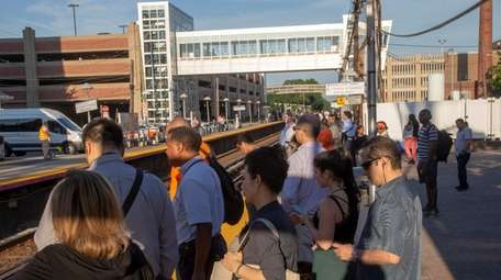 Commuters wait at the LIRR station in Mineola