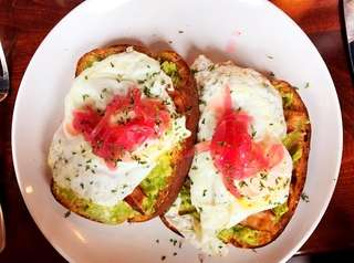 Avocado toast with bacon, an over-easy egg and