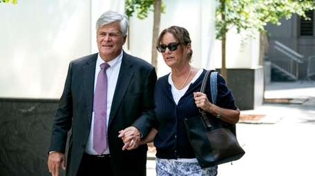 Dean Skelos and his wife Gail walk from
