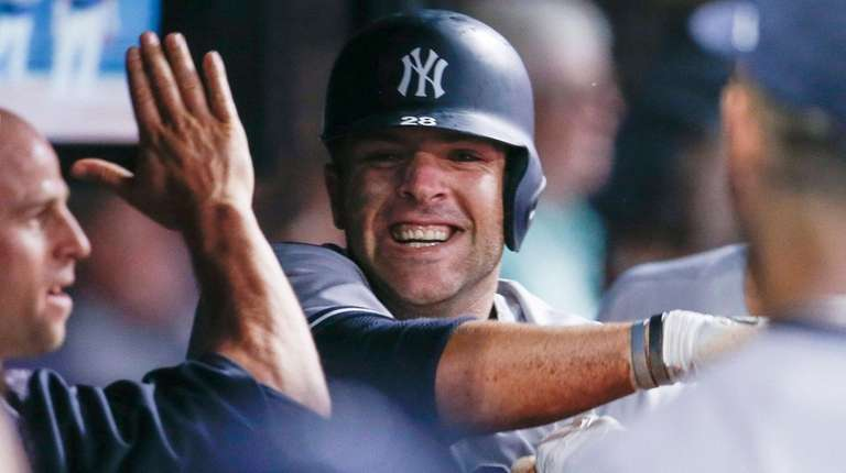 Yankees' Austin Romine celebrates in the dugout after