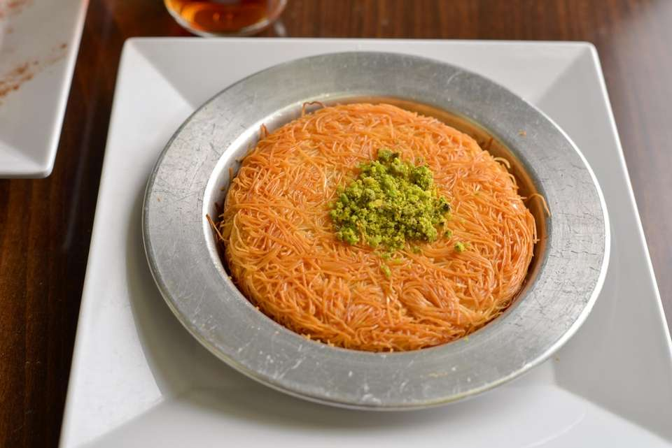 Kunefe, a sweet pastry coated in syrup, topped