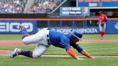 Michael Conforto of the Mets slips and falls