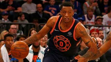 Troy Williams (left) of the Knicks drives to