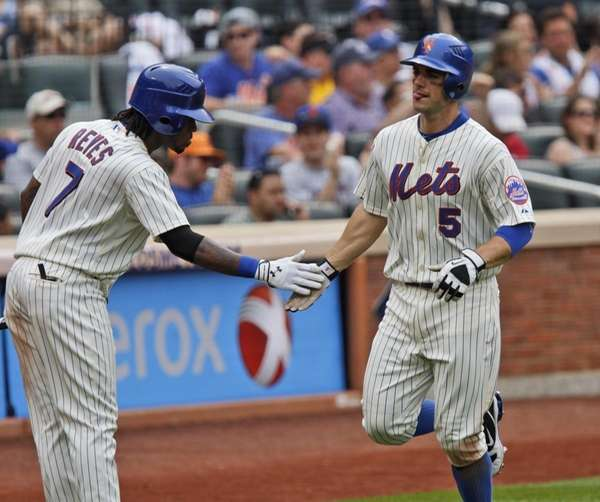 The Mets' David Wright is greeted by teammate