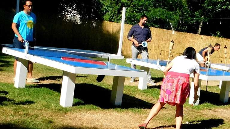 Guests play pingpong at E.M.P. Summer House in