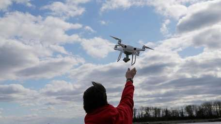 A drone operator helps to retrieve a drone
