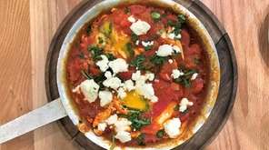 Shakshuka, eggs poached in tomato-pepper sauce, is topped