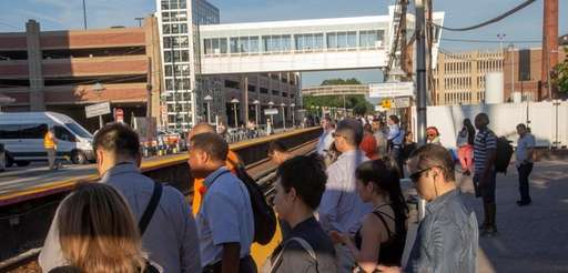 Commuters wait at the LIRR station in Mineola.