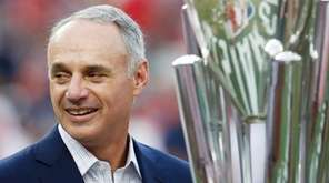 MLB commissioner Rob Manfred stands with trophy before