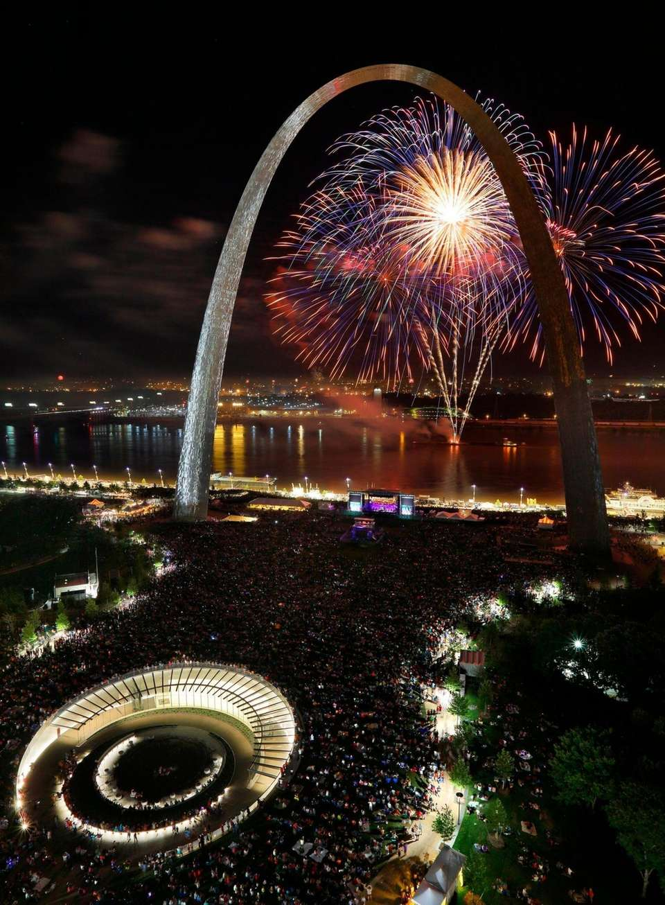 Fireworks explode over the Mississippi River in front