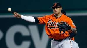 The Orioles' Manny Machado throws to first base