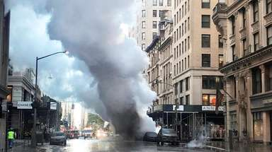 Smoke billows from a steam pipe explosion on
