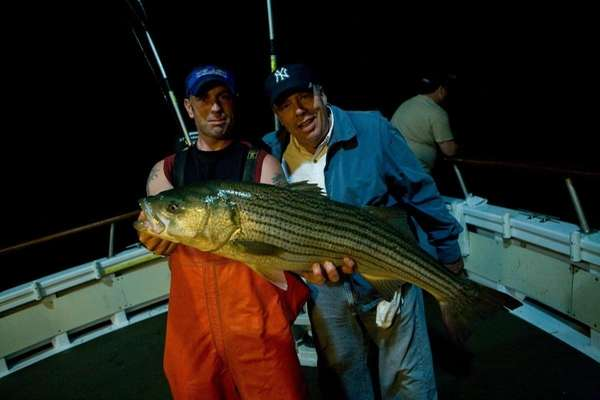 Brian Dunston holds a striped bass caught by