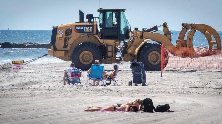 Beach-goers lounge near dune work on the beach