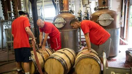 The distillery team fills barrels with bourbon that