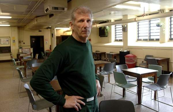 John MacKenzie stands in an inmate visiting room