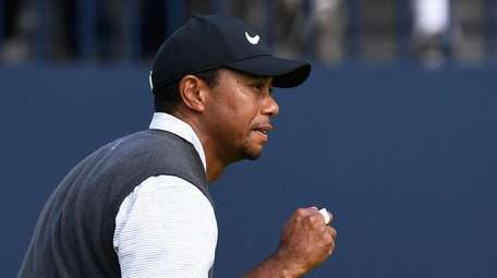 Tiger Woods of the US completes the 18th