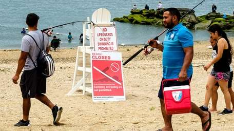 Beachgoers enjoy the water despite health officials advising