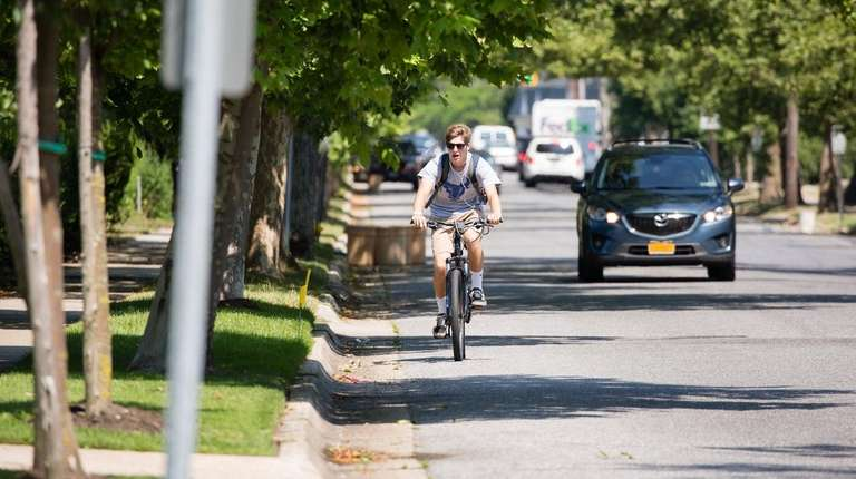 A cyclist rides south on Maple Avenue in