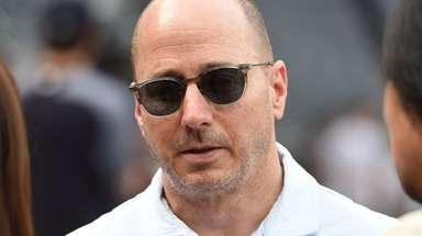 Yankees general manager Brian Cashman looks on from