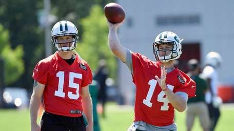 Sam Darnold passes as Josh McCown looks on