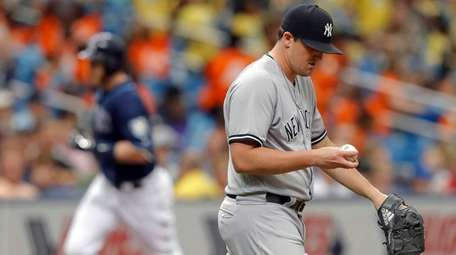 Yankees relief pitcher Jonathan Holder reacts after giving
