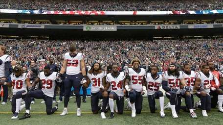 Houston Texans players kneel and stand during the