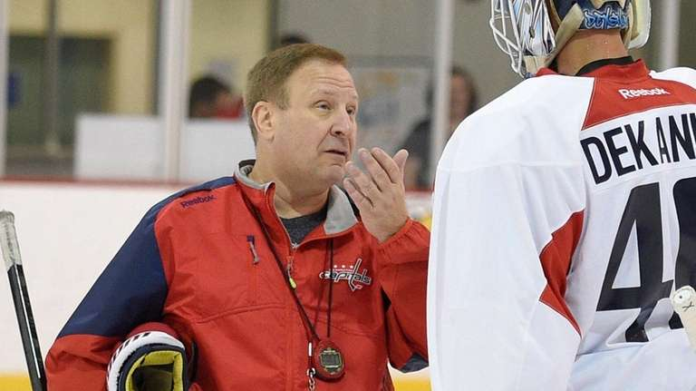 Washington Capitals goaltending coach Mitch Korn, left, talks