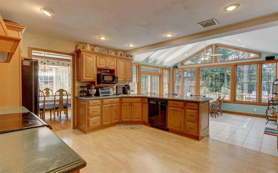 The kitchen features radiant heated floors and vaulted
