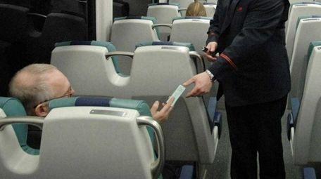 A conductor checks a ticket on the Ronkonkoma