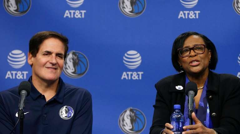 Dallas Mavericks owner Mark Cuban, left, looks on