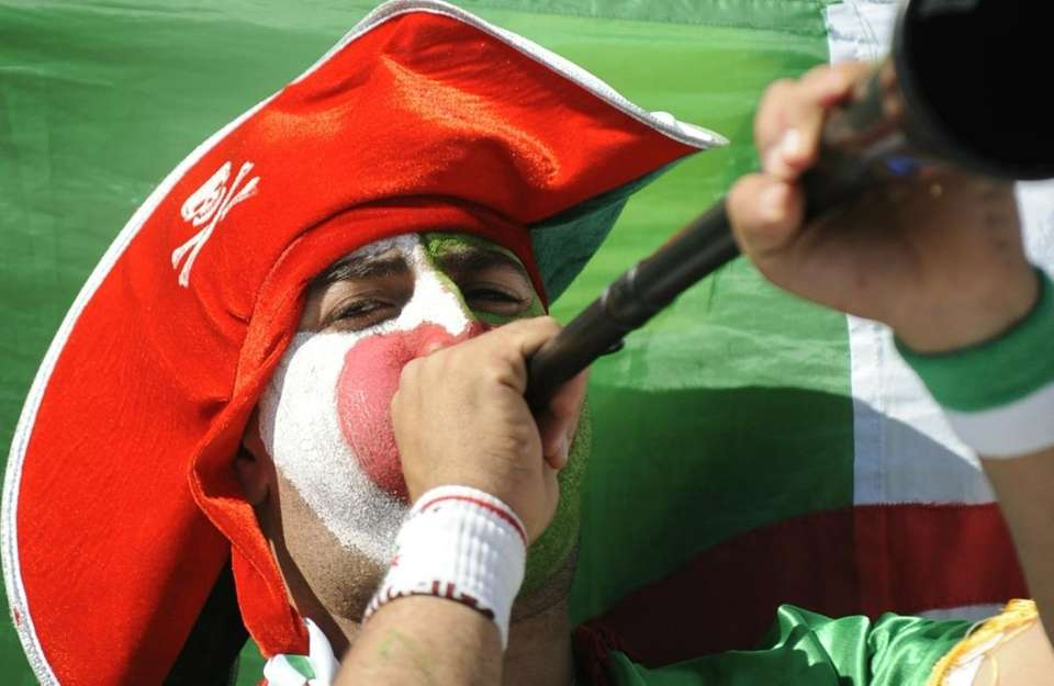 An Algeria fan blows a vuvuzela before the