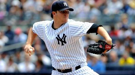 Yankees starting pitcher Phil Hughes throws against the