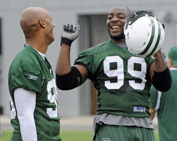 Jets linebacker Bryan Thomas, right, talks with fellow