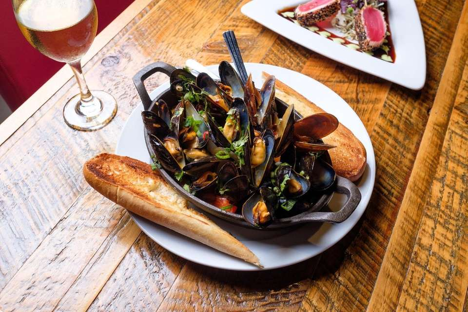Coconut-curry mussels is served with toasted garlic bread