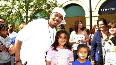 Entertainer Nick Cannon poses with fans during an