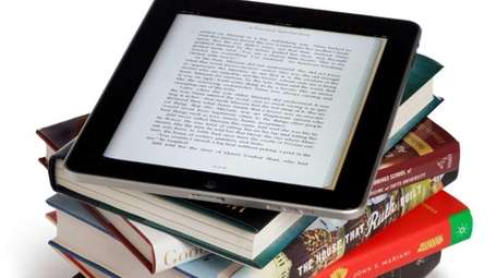 An ipad on top of books.