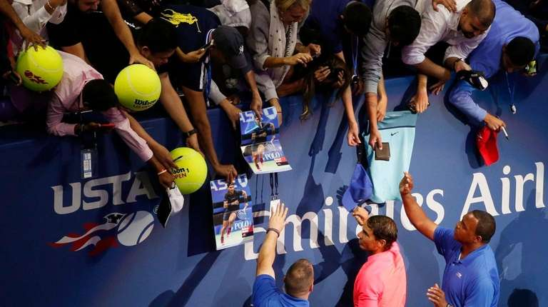 Rafael Nadal signs autographs for fans after beating
