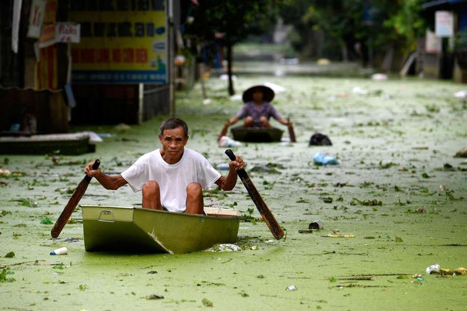 People row in boats through floodwaters in Hanoi's
