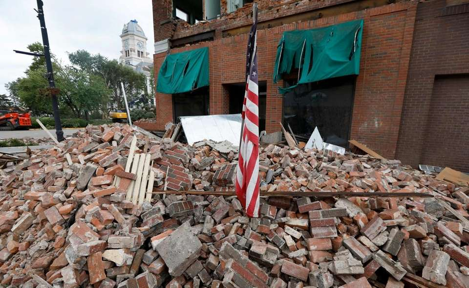 A flag sits in rubble in front of