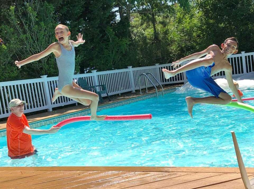 Max and Samantha Cohen have fun jumping over