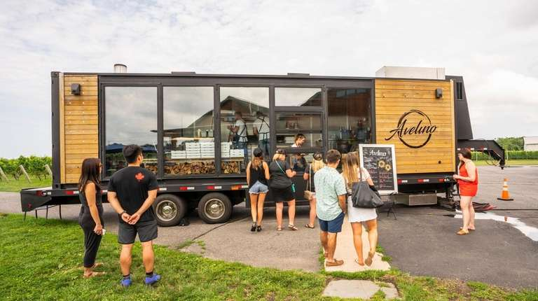 Patrons gather by the Avelino pizza food truck