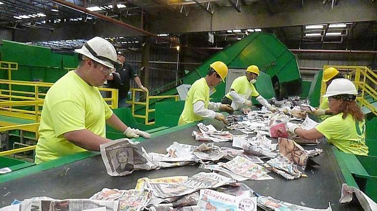 Workers separate trash at Green Stream Recycling in