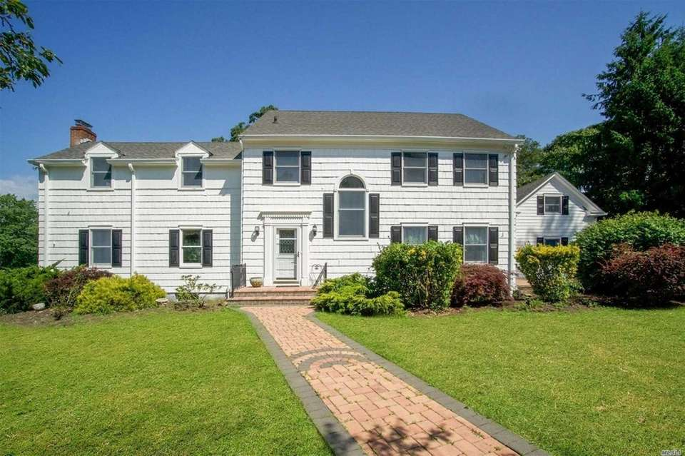 This Bayport Colonial includes six bedrooms and five