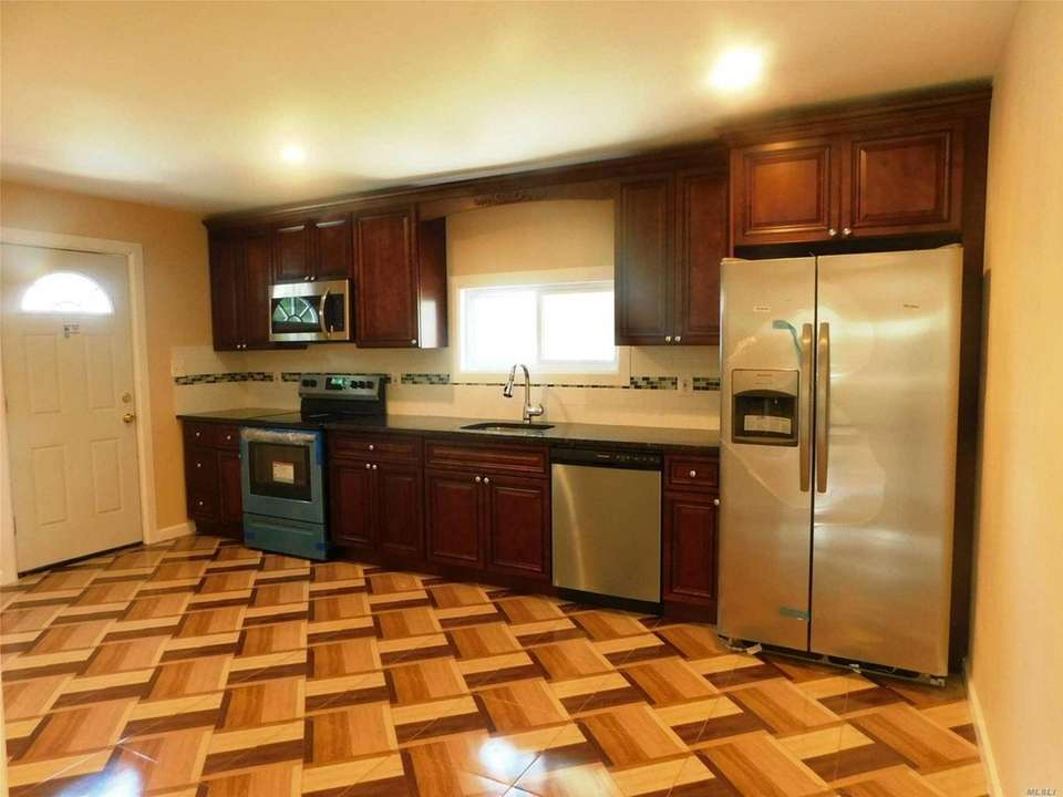 The eat-in kitchen features stainless steel appliances, granite