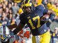 Michigan tight end Tyrone Wheatley pushes away Illinois