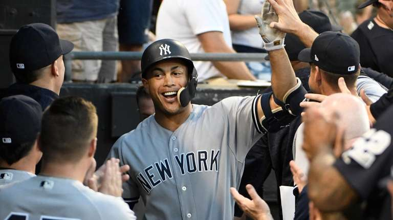 New York Yankees' Giancarlo Stanton, center, is greeted