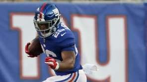 Giants running back Saquon Barkley goes over Cleveland