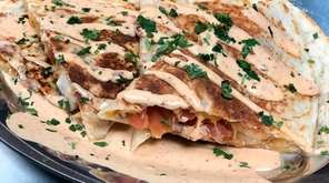 A shrimp quesadilla drizzled with house sauce at